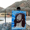 In the back of El Santuario de Chimayó there is a quiet area surrounded by hills where people gather to pray outside. A young man sits in reflection in front of a black wrought iron on display there. He has homemade painting of Jesus hanging on his back. (Photo by Hélène Casanova)