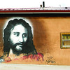 "A wall mural of Jesus Christ photographed in route to El Santuario de Chimayó on the New Mexico State Road 76 in Las Trampas, NM. Signed by a local artist know as ""Felix."" Written in the bottom right are the words, RIP Adrian in reference to the passing of a loved one. Pilgrims in route would see this mural on the side of the road walking to Chimayo. (Photo by Hélène Casanova)"