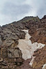 """After crossing this icy gully, Pyramid climbers face the steep, challenging """"green wall"""" above.  A Mountain Goat shows the way.  Colorado Elk Range."""
