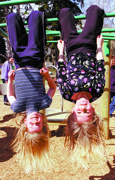 kids hanging out in park 2 in friday dave milne april 19 01 Brooke Hockin, left and sister Mariah spent a sunny Thursday afternoon just hanging around the playground at Fort George Park.
