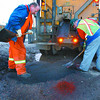 Pothole Patroll1/Wednesday Brent Braaten-April 2/2002  James West, left, anmd Len Massicotte with the City of Prince George streets Divison patch potholes with cold mix on 15th Avenue Tuesday evening. The frezze thaw  cycle has been creating a lot of potholes this spring.
