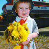 Dandelion Festival/Monday Brent Braaten-May 29/2004  Berrett Williams, 2, holds up his bouquet of dandelions he collect in front of one of the locamotives at the Railway and Forestry Museum Saturday morning during the dandelion festival