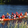 in bloom judges in canoe in friday dave milne july 21 04 Communities in Bloom judges arrive Wednesday at the home of Murry Krause by canoe on the Nechako River dressed as voyageurs. They were welcomed by the Free Trappers firing bvlack powder rifles and were piped ashore by Sheldon Clare