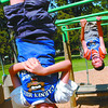 Hanging About/Thursday Brent Braaten-Aug 11/2004  Aiden Carlton, 10, and Brian Nadalin,9, hang on the monkey bars at Rotary Playground in Fort George Park. The youths were there with the Carney Hill Neighborhood association. Paul has story.
