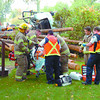Queensway Logging Truck4/Saturday Brent Braaten-Sept 16/2005  Firefighters and paramedics work on the driver of a logging truck that rolled on Queensway Friday morning.