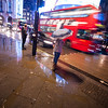 A woman waits in the rain to cross the road at Piccadilly Circus.