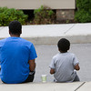 A father and son enjoy a meal on the sidewalk following Habitat for Humanity of Greater Newburgh's dedication of the Spearman and Martinez homes on East Parmenter St. in the City of Newburgh on Saturday, June 14, 2014 to complete the week long Builders Blitz. Hudson Valley Press/CHUCK STEWART, JR.