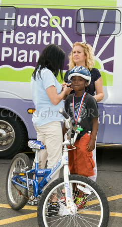 Karen Pfeifer assists Alton with his helmet after he won a bike during Hudson Health Plan's free Bicycle Safety Rodeo on Saturday, August 16, 2014, at Second Baptist Church in Middletown, NY. Hudson Valley Press/CHUCK STEWART, JR.