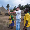 John shooting bow and arrow with native villagers in Rwanda village.