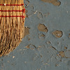 Rustic broom against peeling porch paint.