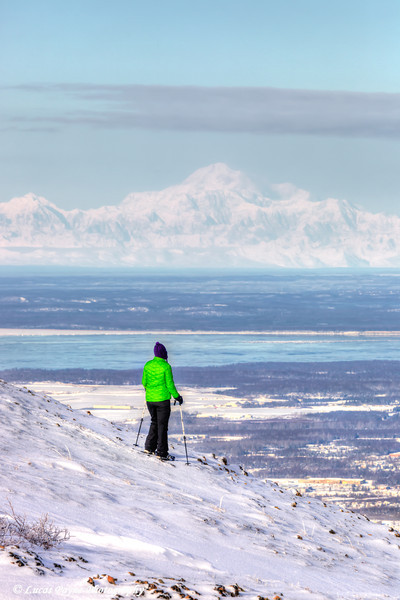 Woman snowshoer taking in the view of Mt. McKinley (Denali) from Blueberry Hill at the Glen Alps area of Chugach State Park, Anchorage, Alaska  February 18, 2013