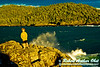 Golden evening light highlights wind driven waves crashing above youth hiker and granite boulders along Lake Superior's Pulpwood Harbor within Pukaskwa National Park (Canada ON Heron Bay)
