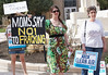 """Woman in brightly colored dress holds sign, """"Moms Say No To Fracking"""" at demonstration, other protesters beside her."""