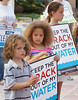 Young children with anti-fracking signs at protest.