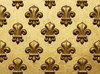 Fleur-de-lis painted in gold in a repeating pattern on a grand entrance to a Paris building. This decorative element represents lilies (or water lotus) is often used a symbol of French royalty.