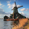 Zaanse Schans Windmills, Zaanstad, Netherlands. With wooden boat and river in foreground.