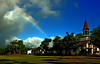 A rainbow over the large grassy area touches the church <br><br>North Shore of O'ahu, Hawai'i