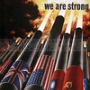 "The flags of the Allies of World War II encircle cannons firing full strength against the Axis powers in an American inspirational poster that declares, ""United we are strong, United we will win."""