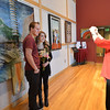 Pam Murphy, right, takes a picture of her daughter Rachel Murphy, 17, center, and Calvin Bollschweiler, 17, in front of artist David Griffin's painting Raigo on display in the lobby of the Audi on Saturday.  February 2, 2013 staff photo/ David R. Jennings