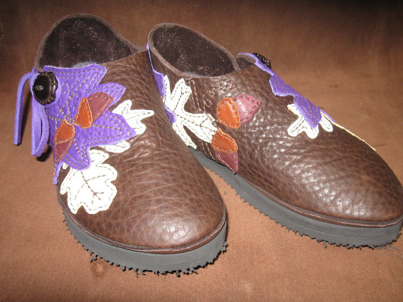 Pam's beautiful shoes are finding their way to her beautiful feet!  Chocolate buffalo one button moccasins, with purple bullhide leaf shaped button trim, creme and palomino deerskin leaf underlays, and a few acorns hanging around... The dark antler crowns finish them off.  Thin cushi with Newflex Vibram soling will ease her way.  Beautiful designed by her favorite guy!
