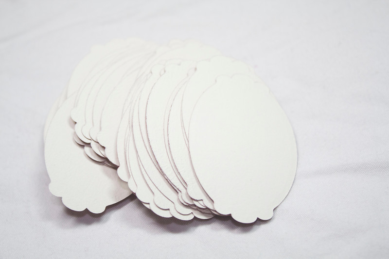 "Back Side Set of 50 Scalloped Oval Tags. 2"" x 1 3/8"". Double-Sided: One side rust in color and the other white. Unsure of make and actually lb but heavy cardstock like 110lb. 1 set available. $2 for the set."