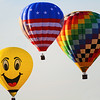 Three hot air balloons including smiley face
