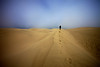 A lone figure walks into the distance at Pismo dunes in California.