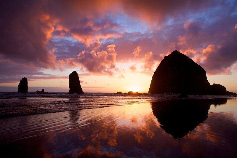 The colors of fiery sunset erupt over Haystack Rock in Cannon Beach, Oregon.