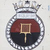 Crest of HMS Bigbury Bay at Dockyard, Bermuda. HMS Bigbury Bay (K606) was a bay class anti-aircraft frigate launched in 1944 and decommissioned in 1959. The ship's history shows that she was a frequent visitor to Bermuda during the 1950's.
