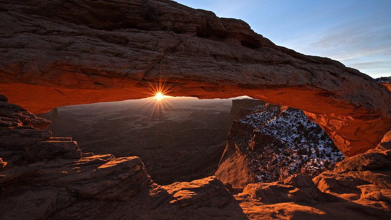 "CLASSIC AT MESA ARCH - 24 January 2015<br /> <br /> Sunburst on Mesa Arch - Canyonlands National Park, File# 1515034<br /> <br /> Link to Full Sized Image:  <a href=""http://www.tom-hill.biz/Galleries/Scenics/Utah/i-vnrL5tc/A"">http://www.tom-hill.biz/Galleries/Scenics/Utah/i-vnrL5tc/A</a><br /> __________<br /> <br /> I've been to Mesa Arch many times.  Seems every time I'm there, it's more and more crowded.  Even though I arrived an hour and half prior to sunrise, I was the fourth person on the arch.  I kind of felt like I was losing my edge by not being the first.<br /> <br /> I have to admit, the photographer I saw later this particular day--described in my blog post from a couple days ago--up on Delicate Arch was the first photographer there this morning.  By the time the sun hit the horizon and I shot this picture, there were about 15 people clustered around the arch trying to get their iconic image.<br /> <br /> Among the group at the arch were these two young Chinese women shooting with their phones and point and shoot cameras.  They were quite giggly when talking each other waiting for the sunrise.  On cue with the light hitting the arch and I making this image, the girls directly behind me gave a loud exclaim, then immediately really started to talk between each other.  Of course, I didn't understand a single word they said, except once.  Being they were directly behind me as I shot this image and saw what I had on the camera's display, one of them said in good english, ""beautiful.""  I nodded approval of her observation.  It was precisely that, beautiful.<br /> <br /> Cheers<br /> <br /> Tom"
