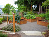 "Vegetable garden made up of steel raised beds laid out in a pleasing geometric pattern. Open steel mesh panel provides perfect support for rambling veggie vines.  Garden Design: Darcy Daniels, Bloomtown Gardens,  <a href=""http://www.bloomtown.net"">http://www.bloomtown.net</a>. Steel fabrication of raised vegetable boxes and fence: Rob Trautmann. Garden contruction: Pete Wilson Stoneworks."