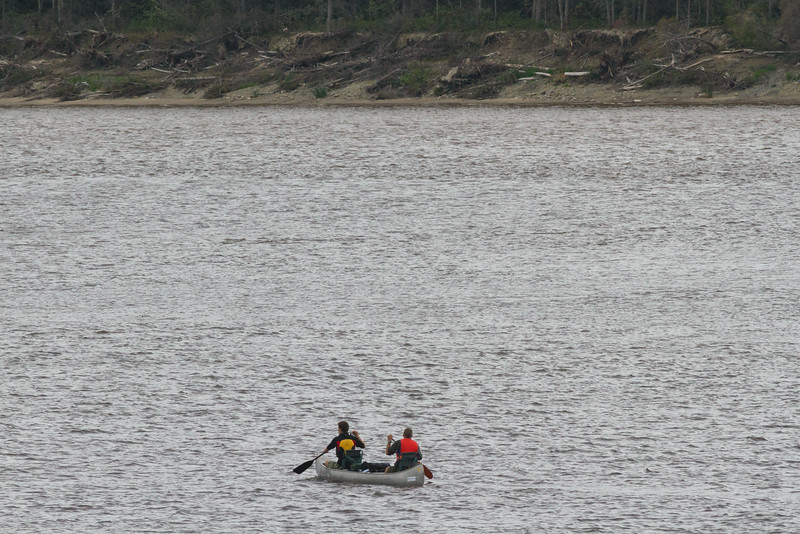 Two people in a paddle canoe. Butler Island in the distance.