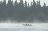 Covered canoe on the Moose River heading downstream on a morning with remnants of fog.