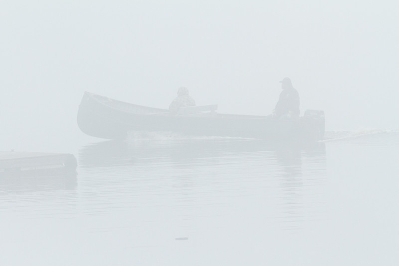 Canoe goes past on a foggy morning on the Moose River at Moosonee.