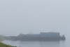 Barges and tug anchored at Moosonee on a foggy morning.