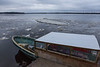Taxi boat at public dock site in Moosonee as ice floats by.