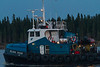 Tug Nelson River heads down the Moose River from Moosonee with a barge in tow on its way north to James Bay.