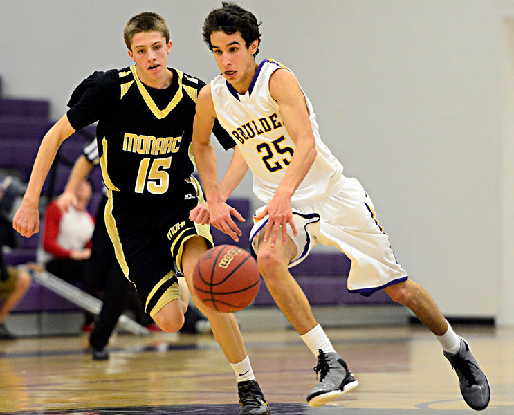 Boulder's Alejandro Rodriguez (25) drives past Monarch's Sam Fredricksmeyer (15) during the game at Boulder High School on Tuesday, Jan. 8, 2013. Monarch beat Boulder 51-49. For more photos visit www.BoCoPreps.com. (Greg Lindstrom/Times-Call)
