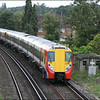 A pair of South West Trains class 458 units (458015 & 458027) pass an old SR plate layers hut as they head into Egham Station with 2C30 (1042 Reading-London Waterloo) - 10 July 2014.