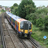 South West Trains class 450 (450010) heads away from Egham Station, just visible in background, with 2S25 (1022 London Waterloo-Weybridge) - 10 July 2014.