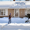 Salisbury: Gary Kamienski uses a snow rake to clean off the thick snow on his Salisbury home yesterday afternoon. Warming temperatures should bring relief combined with a stronger sun to melt the snow. Bryan Eaton/Staff Photo