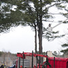 Amesbury: A photographer in a bucket captures workers taking down a giant white pine tree at the 14 Unicorn Circle home in Amesbury of Andrew Ghezzi for a reality television show. Bryan Eaton/Staff Photo