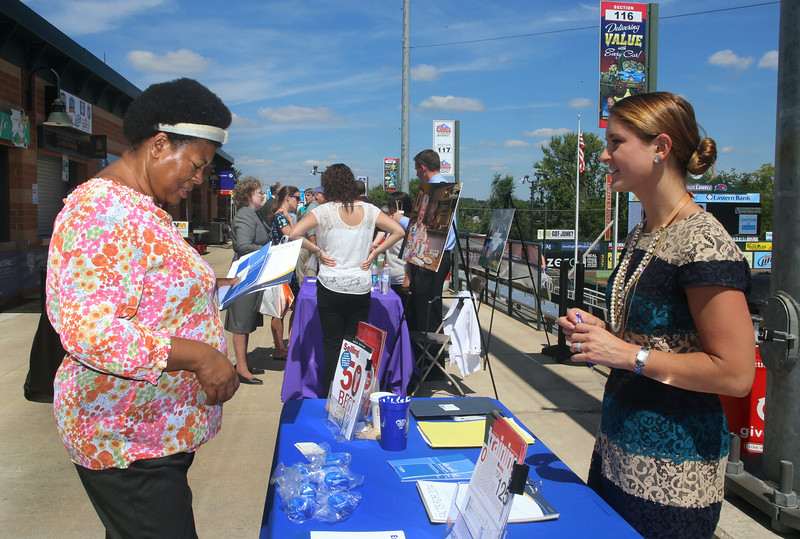Lowell Spinners Job Fair at LeLacheur Park, with about 40 area employers welcoming prospective job applicants. Mireille Audate of Lowell, left, gets information from Danielle Duffy of Manchester, N.H., director of recruitment & selection at Northwestern Mutual in Andover, which does life insurance and financial planning. (SUN/Julia Malakie)