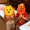 Two kids showing off their lion and tiger masks.