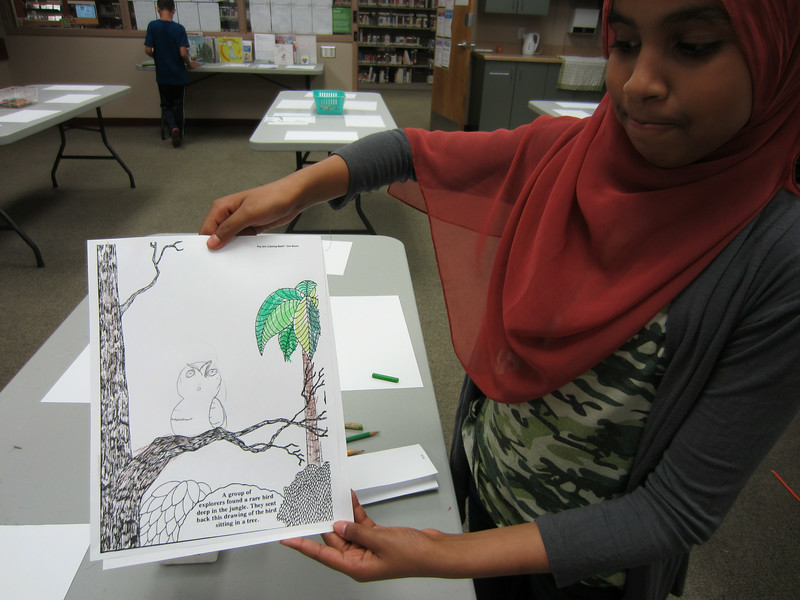 A girl shows off the owl she's drawn on a tree.