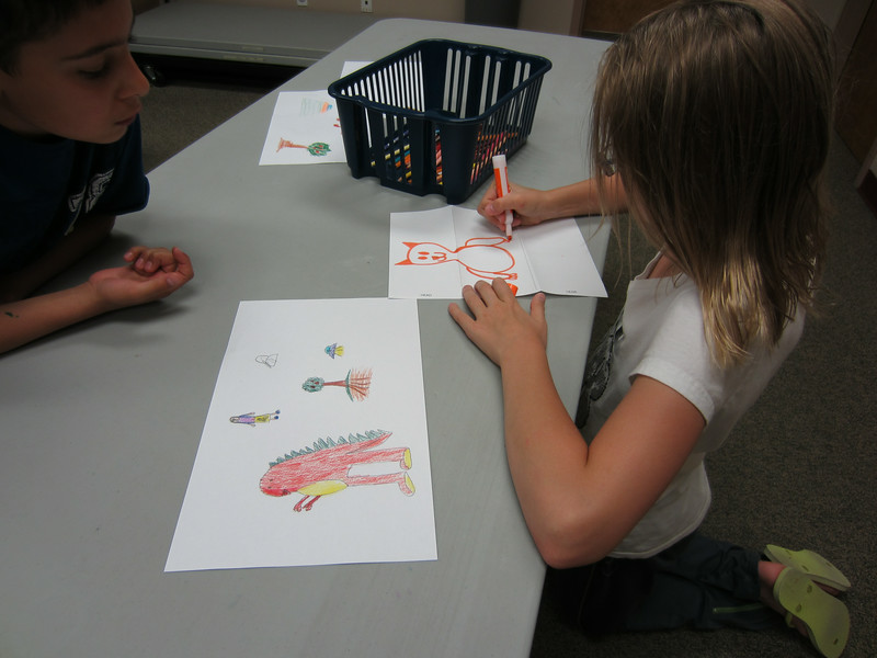 A boy looks on while a girl draws a cat.