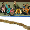The children take turns asking questions about a snake pelt.