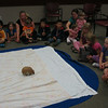The armadillo walks across the floor towards the children.