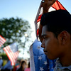 William Bello, 16, of Upland, holds an american flag during a vigil held by members of the Justice for Immigrants Coalition of Inland Southern California (JFIC) Coalition, faith leaders and community members from throughout the region on Wednesday, July 9, 2014 at Murrieta City Hall in Murrieta, Ca. The vigil was held to offer humanitarian support and solidarity with refugee mothers, fathers and children arriving in local communities. (Micah Escamilla/San Bernardino Sun)