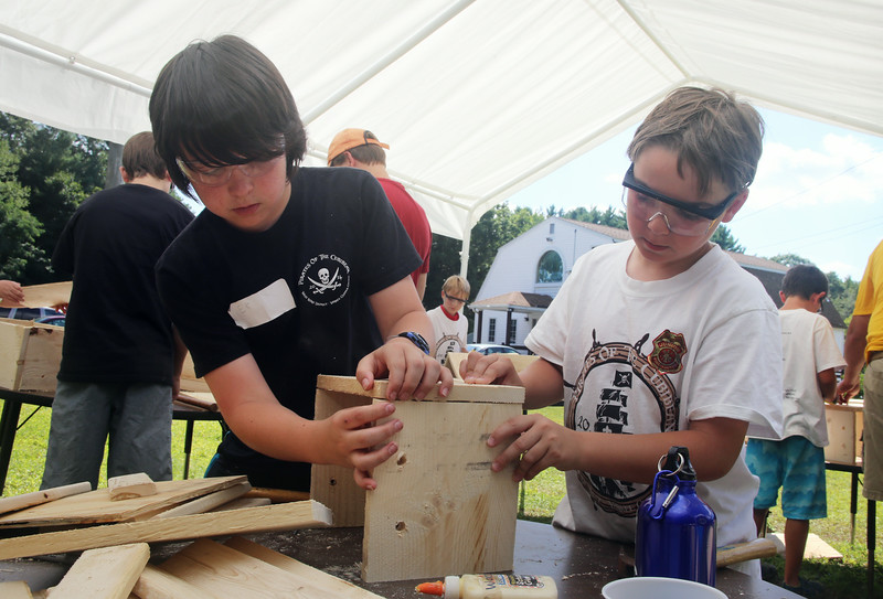 West Wind Cub Scout Day Camp, at the Paul Center in Chelmsford. Almost 200 campers attend the week-long program, with about 50 volunteer Boy Scouts and Girls Scouts helping out with the activities. Volunteer Eli Henry, 12, of Tewksbury, left, helps George Vosnakis, 8, of Chelmsford, assemble his treasure chest in Woodworking. (SUN/Julia Malakie)